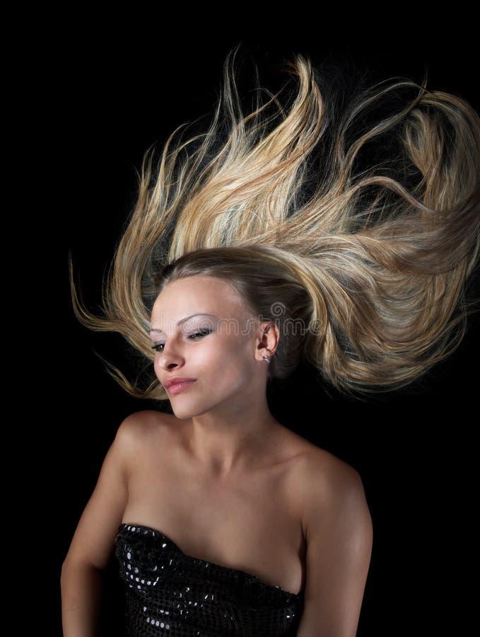 Het blonde vliegen in duisternis stock foto