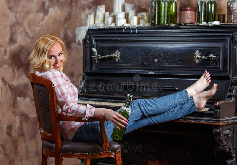 Het blonde vrouw stellen dichtbij retro piano met in de was gezette wijnfles stock foto's