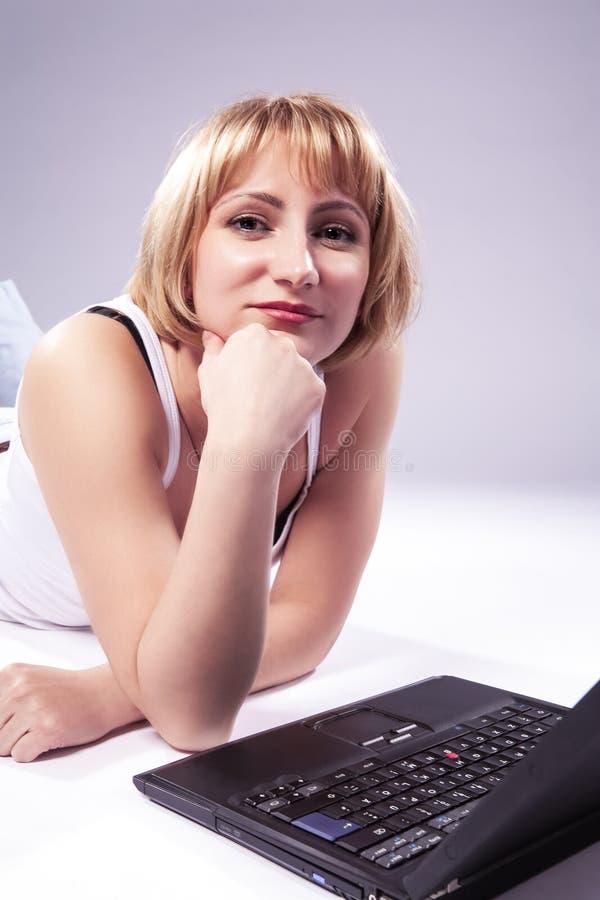 Het blonde Vrouw Stellen met Laptop tegen Witte Achtergrond stock fotografie