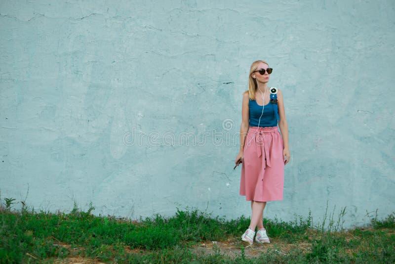 Het blondemeisje in blauwe hoogste en lichtrose rok in tennisschoenen die zonnebril dragen kijkt weg, luistert aan muziek met hoo stock fotografie