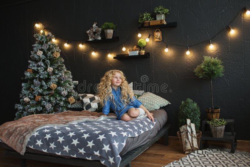 Het blondemeisje in blauwe kleding zit op een bed in Kerstmis donkere ruimte royalty-vrije stock foto's