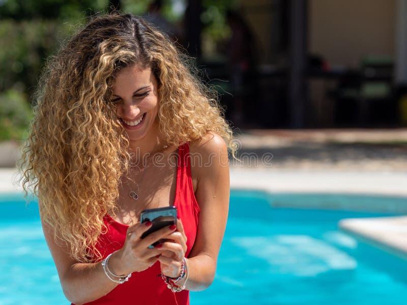 Het blondemeisje gebruikt mobiele telefoon binnen de pool royalty-vrije stock afbeelding