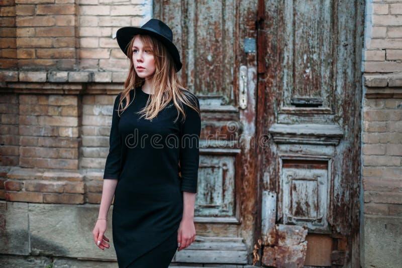Het blondemeisje met lang haar, in zwarte kleding in hoed, bevindt zich op de achtergrond van het uitstekende antieke oude houten royalty-vrije stock fotografie