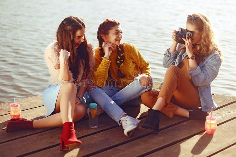 Het blondemeisje neemt beelden van haar donkerbruine meisjes op de oude camera Zij verzenden haar kussen, glimlachen, lach meisje stock afbeeldingen