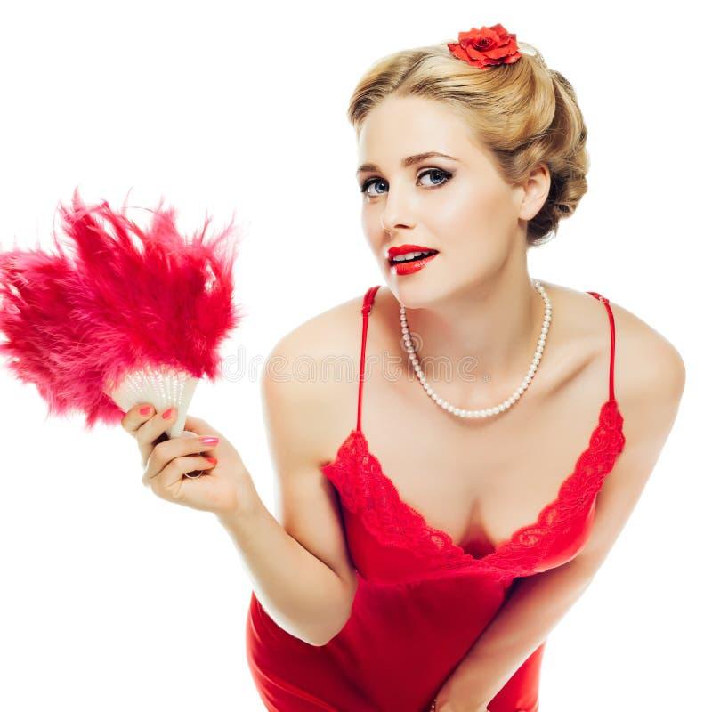 Het blondemeisje speld-omhoog in rode kantkleding met ventilator in haar die hand leunde over en bekijkt speels camera op witte a stock foto