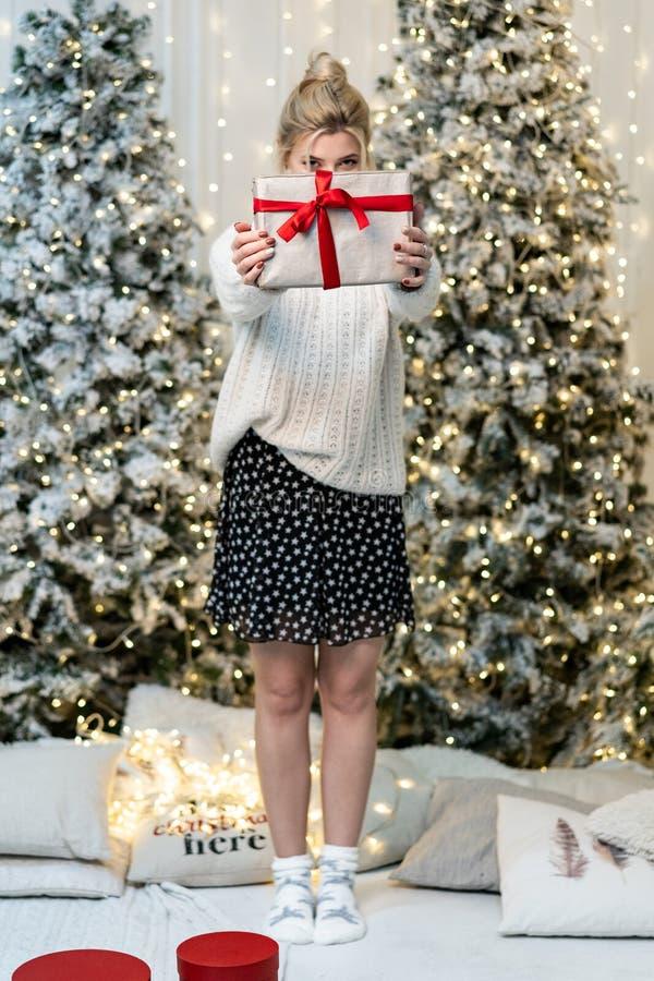 Het blondemeisje in witte sweater verbergt het gezicht achter de gift stock foto's