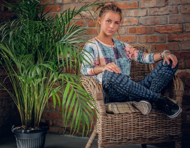 Het blondemeisje zit op een stoel in een ruimte met groene palm royalty-vrije stock afbeeldingen