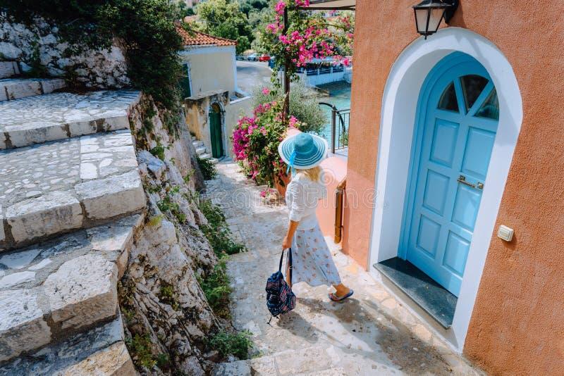 Het blondevrouw die van de reistoerist met zonhoed door smalle straten van een oude Griekse stad aan het strand lopen Vakantie stock foto's