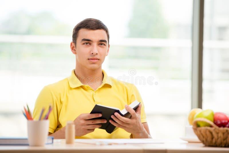Het boek die van de studentenlezing voor examens voorbereidingen treffen stock foto's