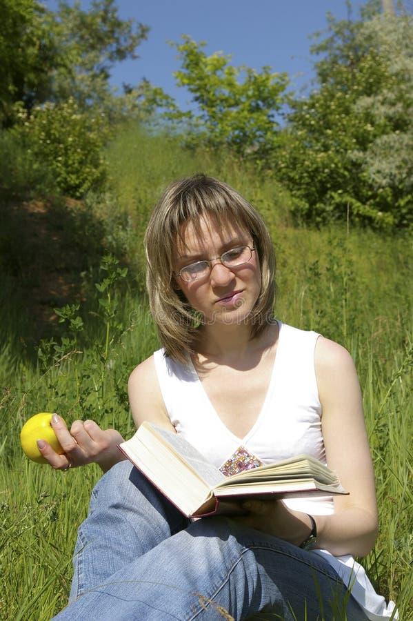 Het boek en de appel van de vrouw stock fotografie