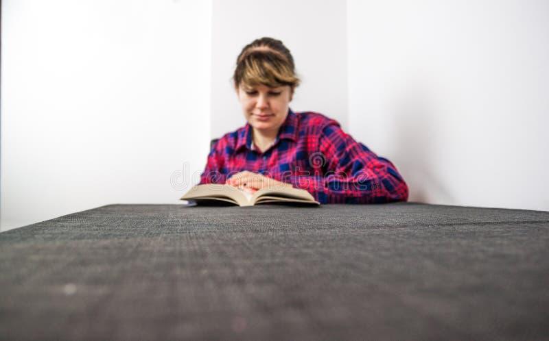 Het boek en de koffie van de vrouwenlezing royalty-vrije stock afbeelding