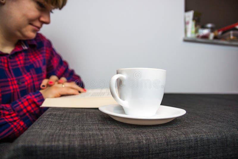Het boek en de koffie van de vrouwenlezing stock afbeelding