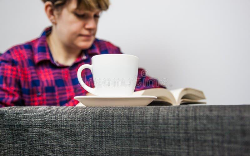 Het boek en de koffie van de vrouwenlezing royalty-vrije stock afbeeldingen