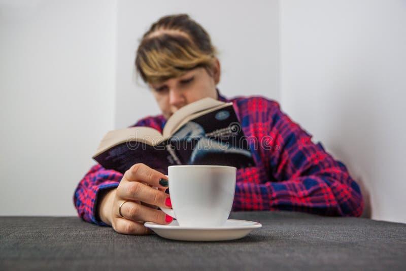 Het boek en de koffie van de vrouwenlezing stock afbeeldingen