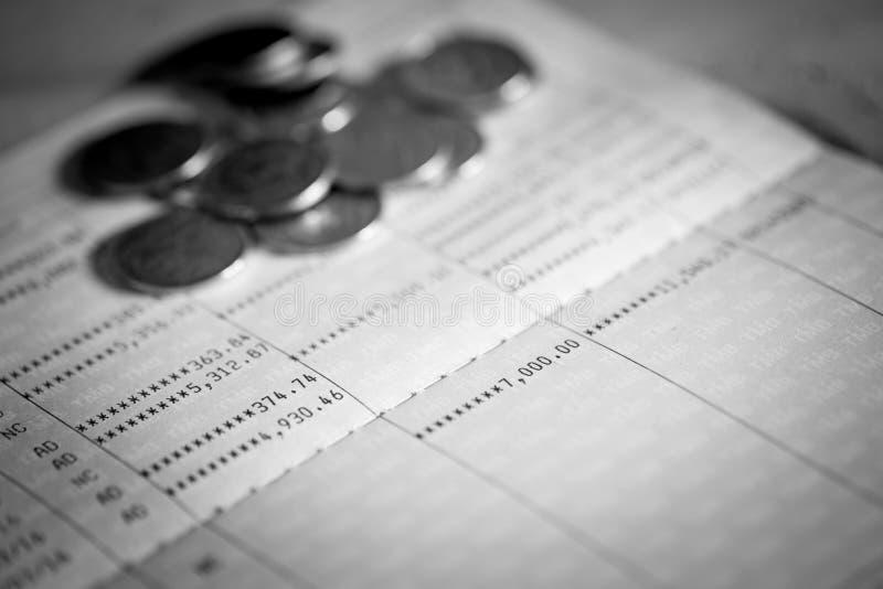 Het boek en de muntstukken van de spaarrekeningbank stock afbeeldingen