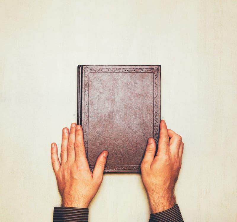 Het boek is hierboven in de handen van een mens van spot omhoog voor tekst, gelukwensen, uitdrukkingen, het van letters voorzien royalty-vrije stock foto