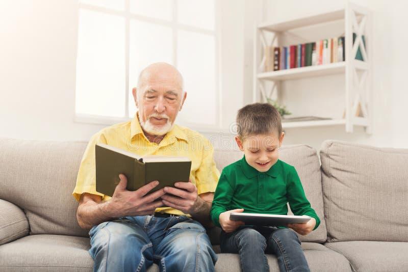 Het boek van de grootvaderlezing, kleinzoon die tablet gebruiken royalty-vrije stock fotografie