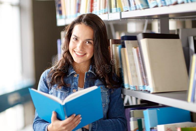Het boek van de het meisjeslezing van de middelbare schoolstudent bij bibliotheek royalty-vrije stock fotografie