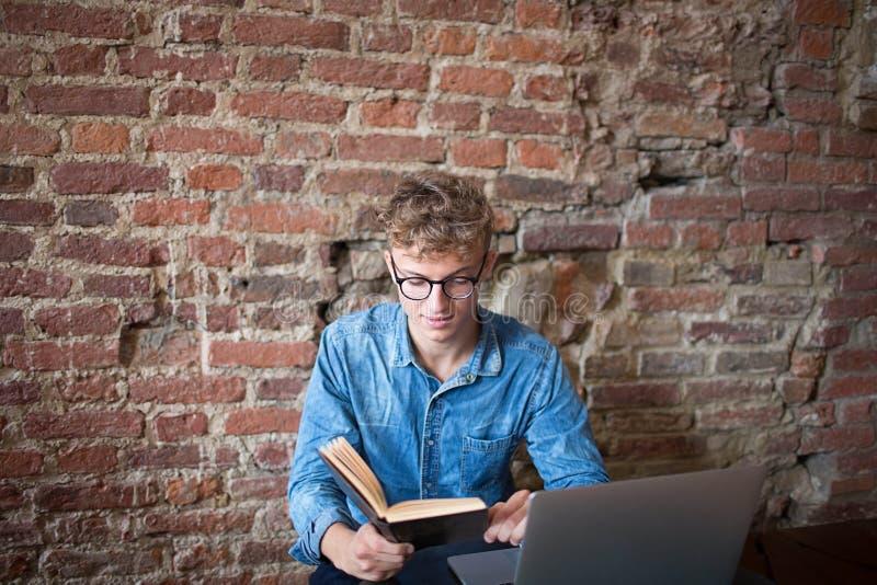 Het boek van de jonge mensenlezing, zitting met laptop computer in recreatieruimte stock foto's