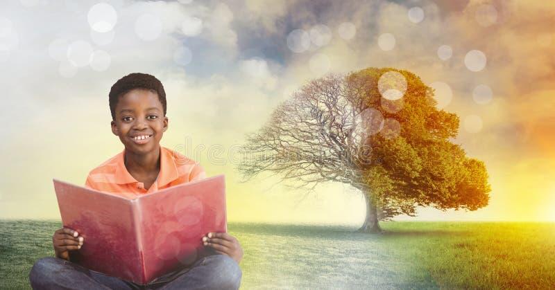 Het boek van de jongensholding met magische surreal seizoengebonden boomverbeelding stock foto's