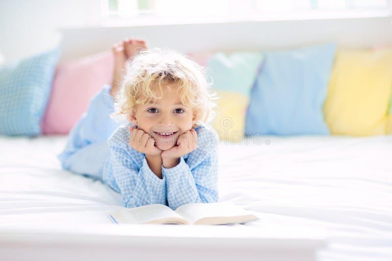 Het boek van de kindlezing in bed Jonge geitjes in slaapkamer worden gelezen die royalty-vrije stock afbeelding