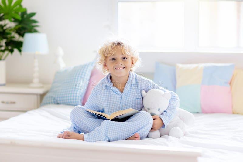 Het boek van de kindlezing in bed Jonge geitjes in slaapkamer worden gelezen die stock fotografie
