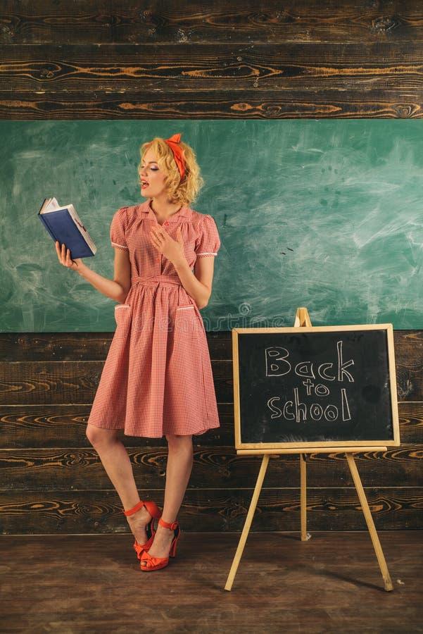 Het boek van de leraarslezing in klaslokaal De mooie vrouw is terug naar school en lezingsboek bij bord Aanbiddelijk en genie stock afbeelding