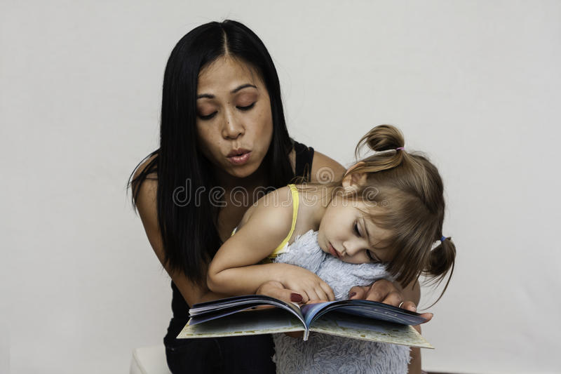 Het boek van de mammalezing aan 3 éénjarigendochter royalty-vrije stock fotografie