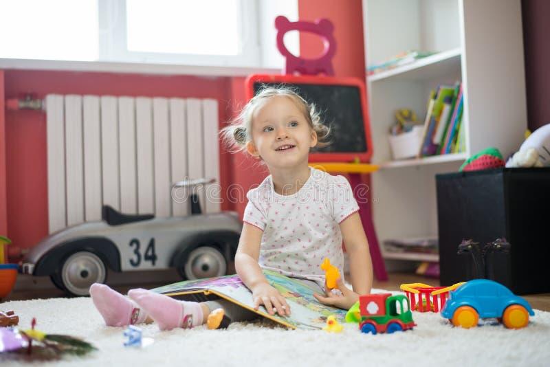 Het boek van de meisjeslezing in de kinderenruimte stock foto