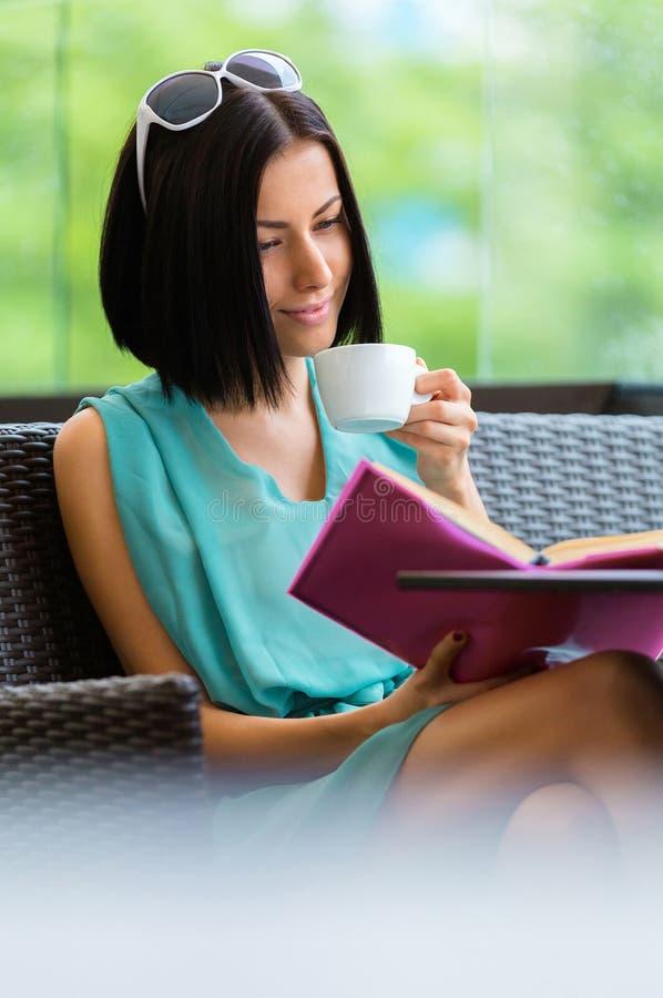 Het boek van de meisjeslezing drinkt koffie bij de koffie stock afbeeldingen