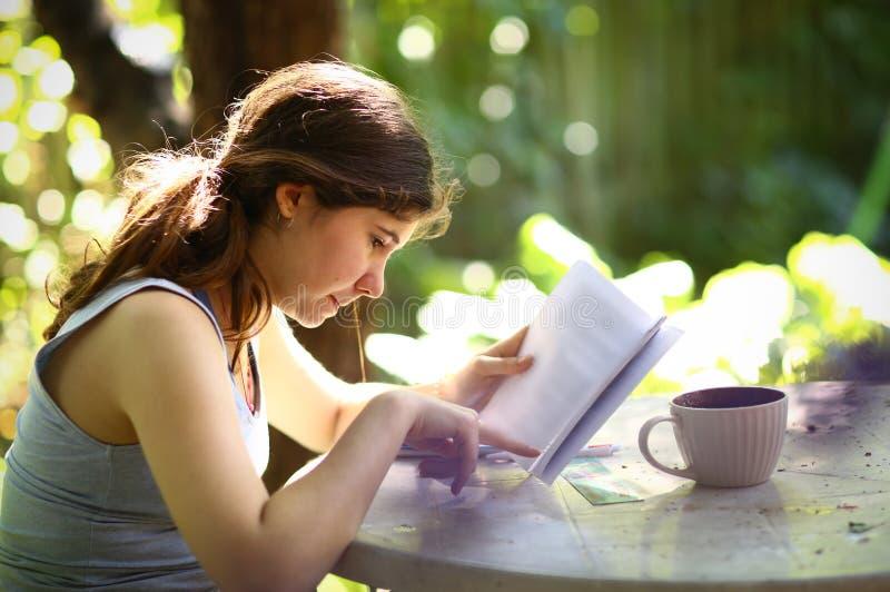 Het boek van de het meisjeslezing van de tienerstudent met theekop stock afbeelding