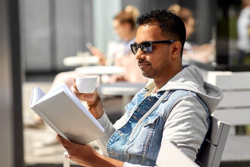 Het boek van de mensenlezing en het drinken koffie bij stadskoffie royalty-vrije stock fotografie