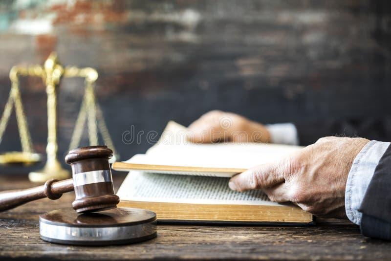 Het boek van de mensenlezing met hamer en rechtvaardigheidsschaal stock fotografie