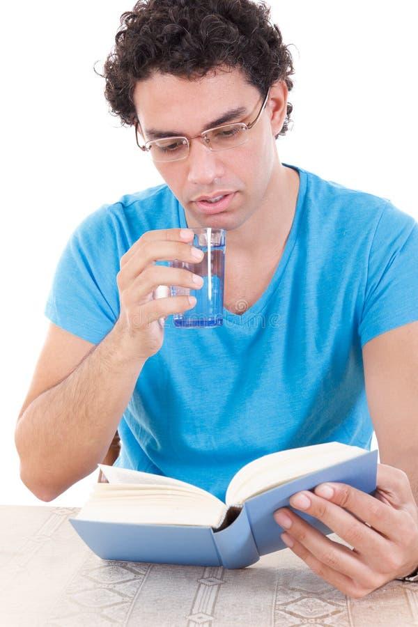 Het boek van de mensenlezing terwijl het drinken van gezond water van een glas stock fotografie