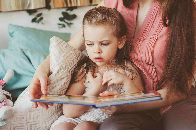 Het boek van de moederlezing aan peuterdochter in slaapkamer voor goede nacht Toevallige levensstijlvangst van gelukkige familie royalty-vrije stock fotografie