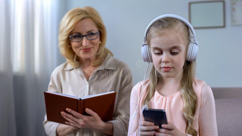 Het boek van de omalezing en het bekijken jong geitje die aan audio in hoofdtelefoons luisteren, concept stock afbeeldingen