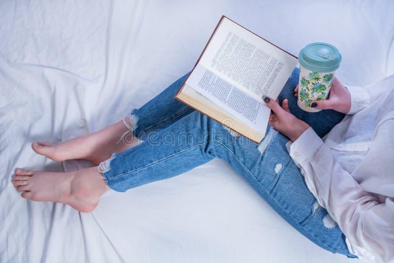 Het boek van de studentenholding op benen met naakte voeten en het lezen en het drinken hete thee in comfortabel bed stock afbeelding