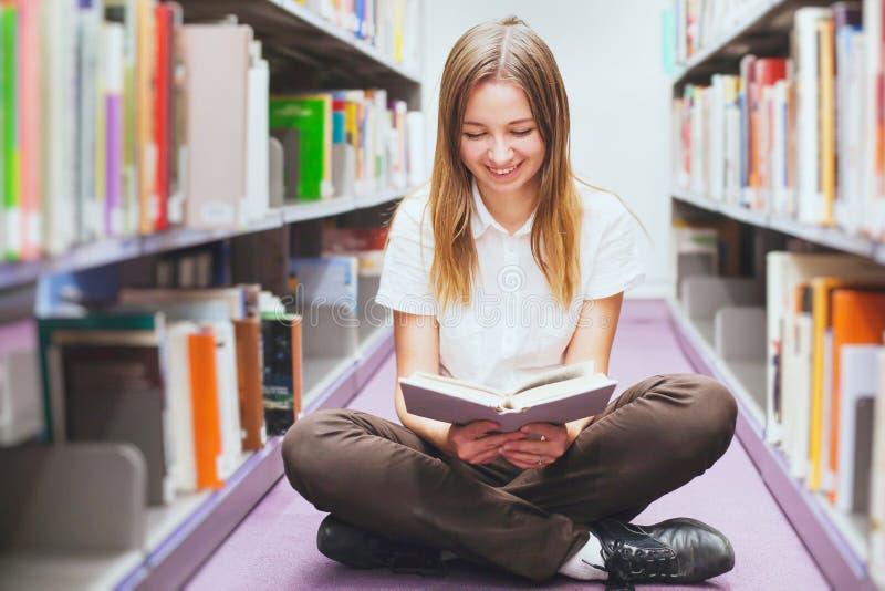 Het boek van de studentenlezing in de bibliotheek, glimlachende gelukkige vrouw, onderwijs stock afbeelding