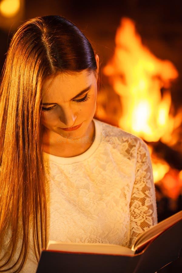 Het boek van de vrouwenlezing bij open haard Het de winterhuis ontspant stock afbeelding