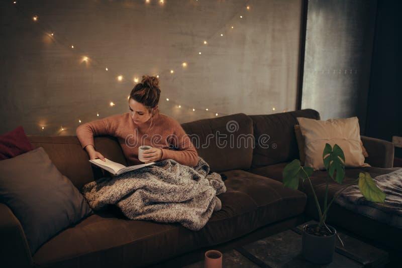 Het boek van de vrouwenlezing in comfortabele woonkamer stock foto's
