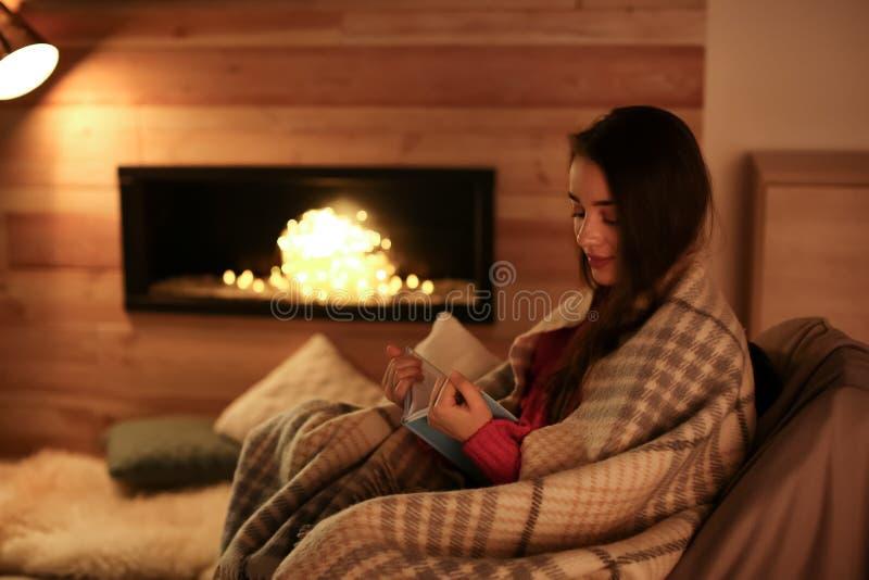 Het boek van de vrouwenlezing dichtbij decoratieve open haard thuis royalty-vrije stock afbeelding