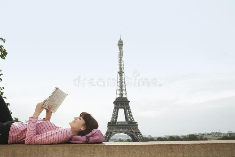 Het Boek van de vrouwenlezing in Front Of Eiffel Tower royalty-vrije stock fotografie
