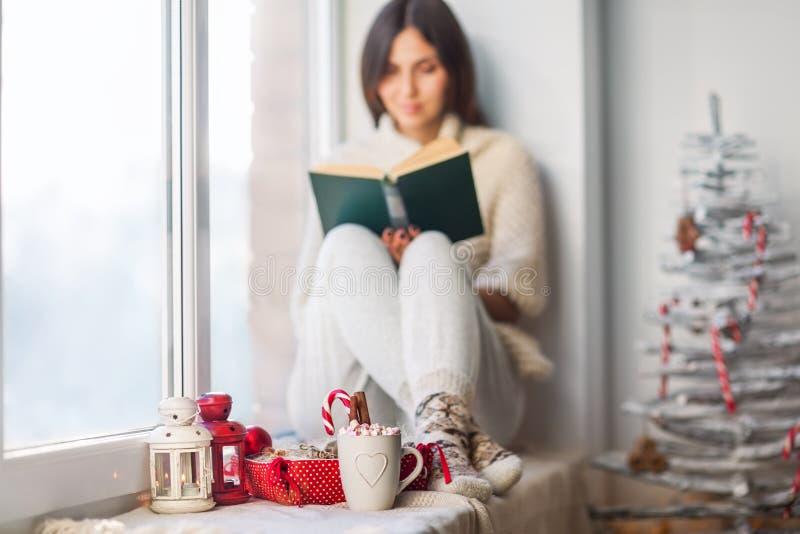 Het boek van de vrouwenlezing in Kerstmis verfraaid huis stock foto's