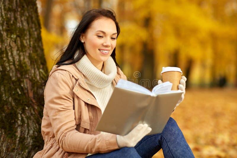 Het boek van de vrouwenlezing met koffie in de herfstpark stock foto