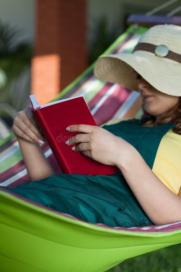 Het boek van de vrouwenlezing op een hangmat royalty-vrije stock foto