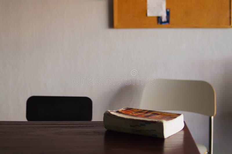 Het boek wordt geplaatst op een bruine houten lijst, is de achtergrond een bruine houten stoel en een witte houten stoel stock fotografie