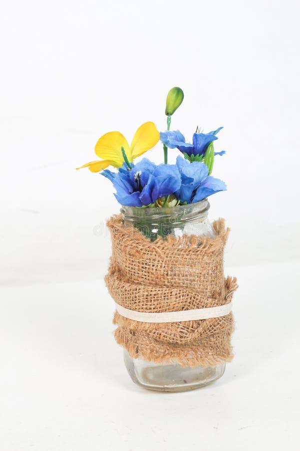 Het boeket met kleurrijke rozen, de bladeren en het stro sieren in glasvaas op witte achtergrond siervaas met bloemen  stock fotografie