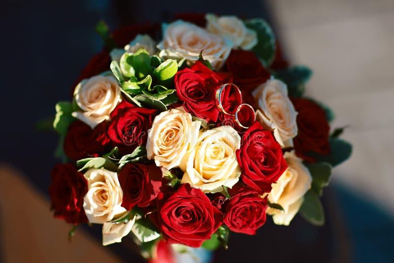 Het boeket van het bloemhuwelijk van witte en rode rozen met gouden bruidhoepels royalty-vrije stock fotografie