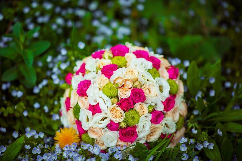 Het boeket van het bloemhuwelijk van witte en roze bloemen met gouden trouwringen van bruiden, op een groen gras met bloemen royalty-vrije stock afbeeldingen