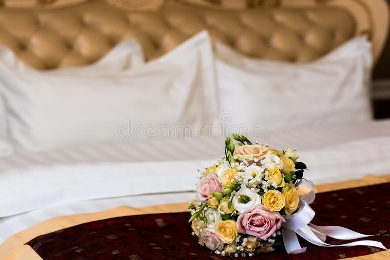 Het boeket van de bruid op het bed De nacht van het huwelijk het boeket van de bruid op het bed Bloemen voor huwelijk Boeket voor stock afbeeldingen